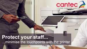 Man using a mobile device to release a print job from a Canon Multifunctional Printer. Two colleagues having a pleasant discussion, sitting at a table in the forefront of the picture.